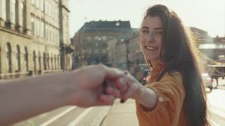 Beautiful smiling long-haired woman holds male hand leading him down the city street. The girl leading a man forward to the adventure. Follow me concept, love story, romantic atmosphere.
