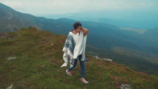 Beautiful young girl in a sport outfit wanders down mountain hills covered with violet flowers. Adventure, relaxation, pure nature. Indie look, hipster. Fresh air, strong wind.