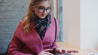 Beautiful young girl in a stylish glasses and pink coat sitting alone in the café, flipping the magazine then looking towards the camera and happily smiling. Leisure time, active lifestyle.
