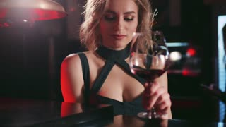 Beautiful young woman in a luxurious dress sitting by the bar, holding wineglass and sharing an alluring smile right towards the camera. Romantic atmosphere. Natural beauty, bachelorette.