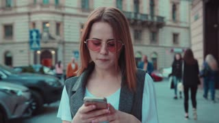 Beautiful young woman in stylish outfit walks down the crowded city, uses her smartphone, gets the message, looks sad and disappointed. Bad news, negative mood, feeling lonely. Female portrait