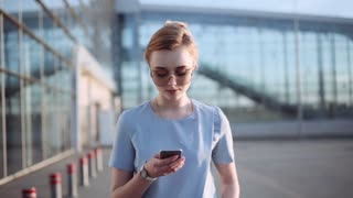 Beautiful young woman walking down the airport, looking around and using her smartphone. Trendy look, formal outfit, stylish sunglasses. Active lifestyle, motivation goals, blogger.