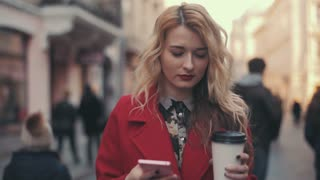 Business woman in red coat with coffee walking in the city and communicate via smart phone (phablet). Steady cam shot.