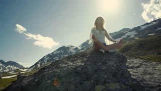 Calm girl is meditating in the mountains, bright sunshine on the background.