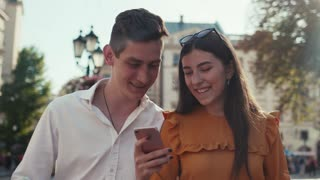 Cheerful couple actively using mobile phone, and smiling while walking down the city street on a bright sunshine. Technologies, social networks, being online. Romantic atmosphere, love story.