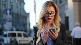 Close up view of a beautiful nerdy like serious businesswoman with red lipstick using her cellphone, she gets the message, and reacts happily to it, smiling brightly and texting back. Social networks.