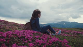 Close up view of a beautiful young woman with a backpack sitting on the top of mountain hill in blooming lavender flowers. Pure nature, stunning scenery. Cloudy weather, active lifestyle.