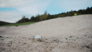 Close up view of a golf ball lying in the sand then player hits it with a golf club, it flies away. Hobby, entertainment, sport. Successful lifestyle, championship