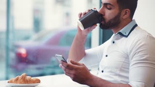 Close up view of a man drinking a coffee, checking his mail, smiling and texting back online. Online communication, social networks. Having fun in a cafe.