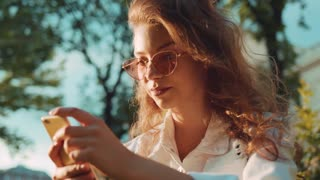 Close up view of a stylish young woman actively using her smartphone while sitting on the grass and having a break in the park on a bright sunlight. Fashionable outfit, browsing the internet