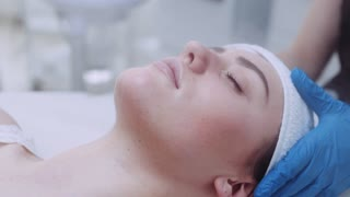 Close up view of a young attractive woman with closed eyes, lying on the cosmetologist's table and having the steam cleaning procedure of the face. Taking care of the health, luxury spa.