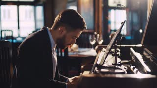 Close up view of an old-fashioned bearded pianist playing the fortepiano in a deserted restaurant. Enjoying the music, jazz. Elegant outfit. Romantic atmosphere.