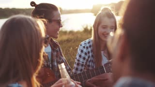 Close up view of attractive young girl and boy holding the guitar talk to their friends, joking while having a picnic at the riverbank, laughing happily in a bright sunlight. Bright sunset.