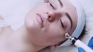 Close up view of beautiful female face being massaged with hardware cosmetology massage tool. Skin care, body care. Active lifestyle, therapeutic procedure, electro-stimulation.