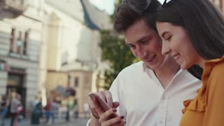 Close up view of beautiful long-haired young woman holding smartphone, and handsome man touching screen, both laughing. Social networks, vlogs, modern technologies, gadgets. Love story