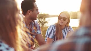 Close up view of beautiful young girl and boy in sunglasses talking to their friends while having a picnic at the riverbank, laughing heartily in a bright sunlight. Bright sunset, having leisure time.