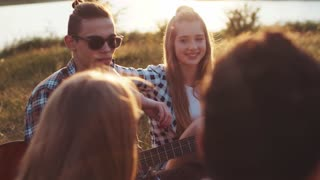 Close up view of beautiful young girl and boy talking to their friends while having a picnic at the riverbank, laughing heartily in a bright sunlight. Bright sunset, having leisure time.