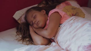 Close up view of cute long-haired child sleeping in her bed, she wakes up, stretches and smiles to the new day. Sunshine, morning, feeling good, holidays
