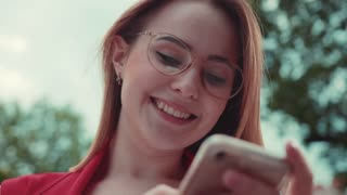 Close up view of cutely smiling young woman in nerdy like glasses standing outdoors, actively texting messages, smiling towards the screen. Browsing the internet, social active, blogging, instagram.