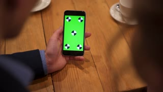 Close up view of man's hand using the phone in the café. Modern life, businessman, greenscreen. Camera stabilizer shot.