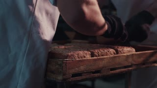 Close up view of man's hands putting steaming loaves of hot ready-made bread onto the cooling rack in bright sunshine. Team work, cooperation. Delicious nutrition, bread-baking manufacture.