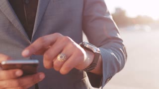 Close up view of strong man's hand with luxurious accessories checking time via smart watch, upgrading it in bright sunlight. Being in a hurry, waiting for arrival. Contemporary technologies.