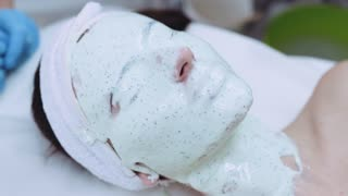 Close up view of woman's face completely covered with organic white beauty mask. Relaxation, enjoying spa. Body care, skin care, pampering. Luxury cosmetics, facial therapy, modern salon.