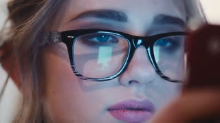 Close up view of young pretty blue-eyed girl in vintage glasses attentively using her cell phone for texting the sms. Web serfing, social communication. Electronic devices, modern technologies.