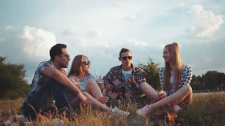 Company of friends having picnic by the fire, actively joking, laughing, one guy plays the guitar, everybody toasting and drinking beer. Friendship goals, having fun. Adventure time.