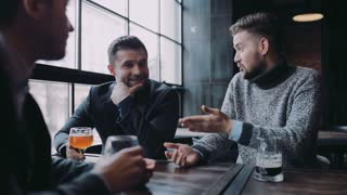 Company of three friends having an active discussion while sitting in the bar, they laugh and raise their glasses to toast, drink the beer. Man's club, male traditions. Active lifestyle.