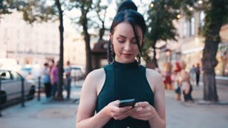 Confident attractive blue-eyed brunette woman in a stylish outfit walks down the central city's street, uses her phone, looks around, actively messaging.