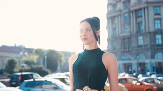 Confident attractive brunette woman in a black dress walking down the city street and seductively looks right to the camera, moving to it. Modern woman, playful mood.