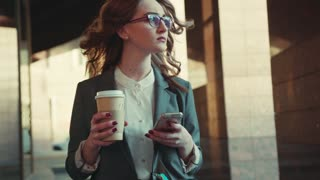 Confident businesswoman walks out of the office, using her smartphone and sipping coffee. Luxury, successful lifestyle, working hard, modern communication. Female portrait, sun lens