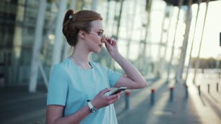 Confident young woman in a stylish look, holds her mobile phone, touches her sunglasses, looks around and crosses the street. Sunny weather, no people around. Cheerful mood, positive emotions