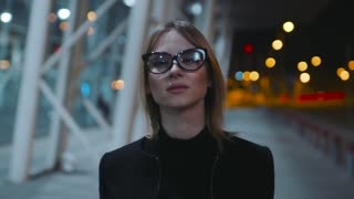 Confident young woman in the glasses with black rim and dark clothes is walking near the business center in the evening. The girl looks around the place.