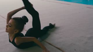 Cute and flexible little girl performing the gymnastics, does forearm stand split, rolls on the floor and stands up. Contemporary body art, being fit and healthy. Modern kids, favorite hobby.