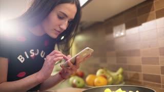 Cute black-haired girl in pajamas has just cooked a breakfast at home. She makes some photos of the food from different angles on her smartphone.