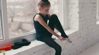 Cute little ballerina puts on her ballet shoes by the window in a modern specious ballet school. Go into sport, active lifestyle. Classic ballet training. Having fun, cheerful mood.