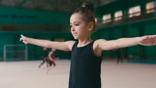 Cute little girl practices stretching in sport school, performs ballet dance pa. Healthy lifestyle, positive emotions. Strong person, active leisure time.