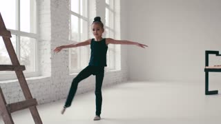 Cute little girl with twisted hair in a black sport uniform does the split in a ballet studio. Training time, keeping balance. Cheerful mood. Active lifestyle. White walls, modern studio interior.