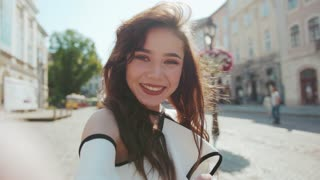 Cute smiling woman poses to camera, acts cheerfully, shows peace sign in the central square. Cuteness, vlogging, social networks. Talking selfie. Female portrait