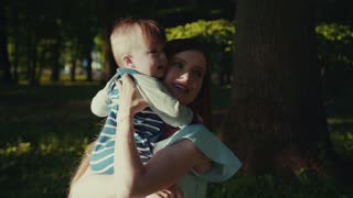 Elegant smiling young mother in a light blue dress holds on her hands and plays with her sweet smiling baby-boy in a park, under the tree. Happy together, joy of a lifetime. Family portrait