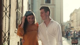 Embracing cheerful young couple in love walking down the city street, talking with each other and happily laughing. Positive emotions, romantic atmosphere, joy of life. Love story. Sun lens