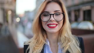Extreme close up view of a beautiful blonde woman in a formal trendy look, with red lipstick and glasses standing in the city center and happily smiling towards the camera.