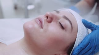 Extreme close up view of a beautiful female's face with closed eyes being cleaned with steam therapy in beauty spa. Enjoying the spa, professional cosmetology tool. Being beautiful.