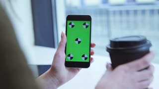 Female hand holds the device with green screen, drinks coffee, and slides the screen up. Passersby on the background.