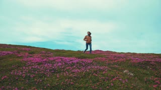 Fit young woman in jeans wear walks down the flowered blossoming mountain hill, takes of her backpack, continues walking. High snowy mountain peaks on the background. Wilderness, being free and happy