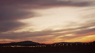 Footage of a 4 engine jumbo jet plane landing in shining small airport. Airport lights on the background. Outside shooting, camera stabilizer shot.