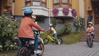 Four cool children in helmets riding their bikes in the yard. Beautiful house on the background. Cozy atmosphere, having fun, adventures, games