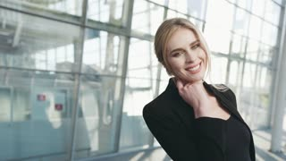 Gorgeous blonde woman in a black outfit looks right towards the camera and shares a beautiful smile. Airport terminal (business centre) on the background. Female portrait, cheerful mood. Modern woman.